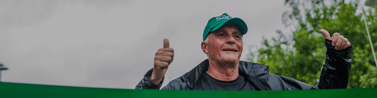 Older man in a green Sage baseball cap and black raincoat giving a thumbs-up