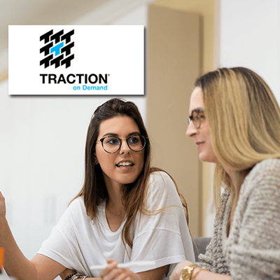 2 women talking with Traction on Demand logo in background
