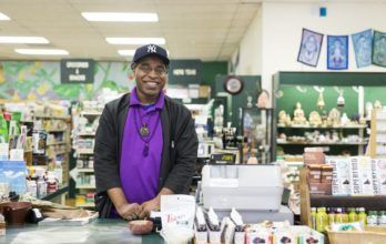 man stands in a grocery store in north america wearing a new york yankees hat
