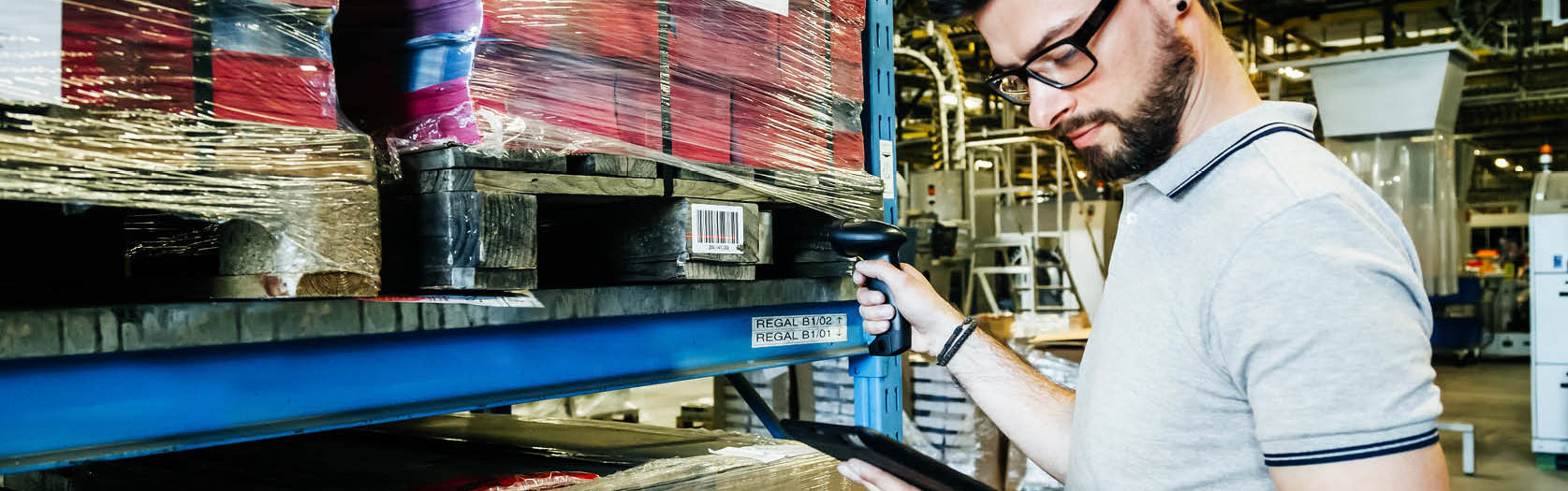 man tracks barcodes and logistics in an erp software warehouse with coloured packages