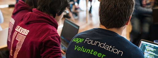 Sage foundation volunteer helping two students work on a laptop