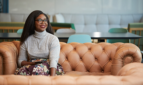 Smiling woman with glasses and a flowery skirt sits on a leather sofa in a café