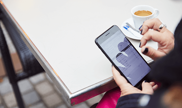 Woman's hands using a smartphone at a table