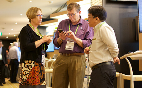 Three business leaders talk at a busy industry event