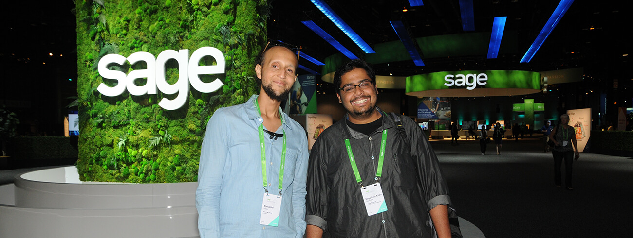 Two Sage delegates pose in front of the Sage logo at an industry event