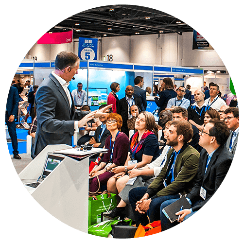 Smartly-dressed man addresses an audience at a busy industry event