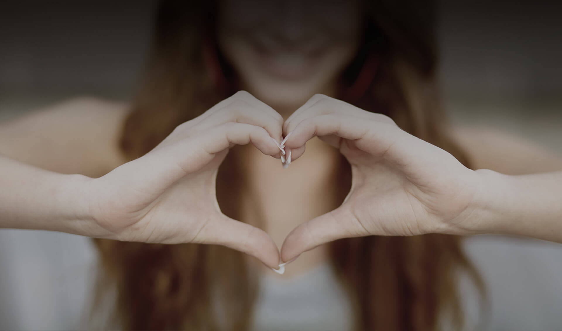 Woman holding her hands together to form a heart shape