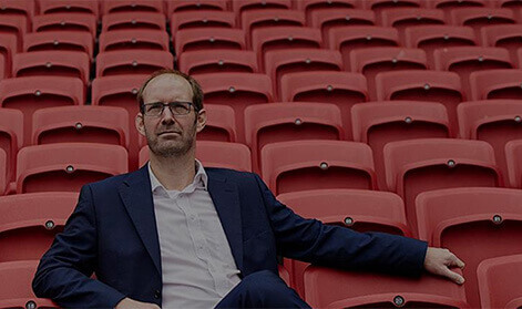 Smartly-dressed man sitting in a row of empty red seats in a sports stadium