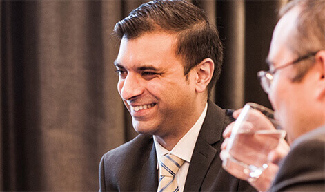 Ambitious looking businessman in a suit and tie smiling while his colleague drinks water from a glass