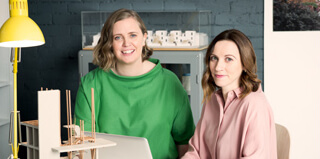 Two fashionably dressed businesswomen sit at a desk in a trendy office