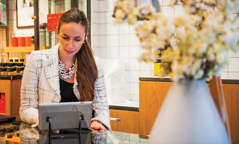 well-dressed woman in a light blazer and pearl necklace using a tablet at the glass counter of a shop