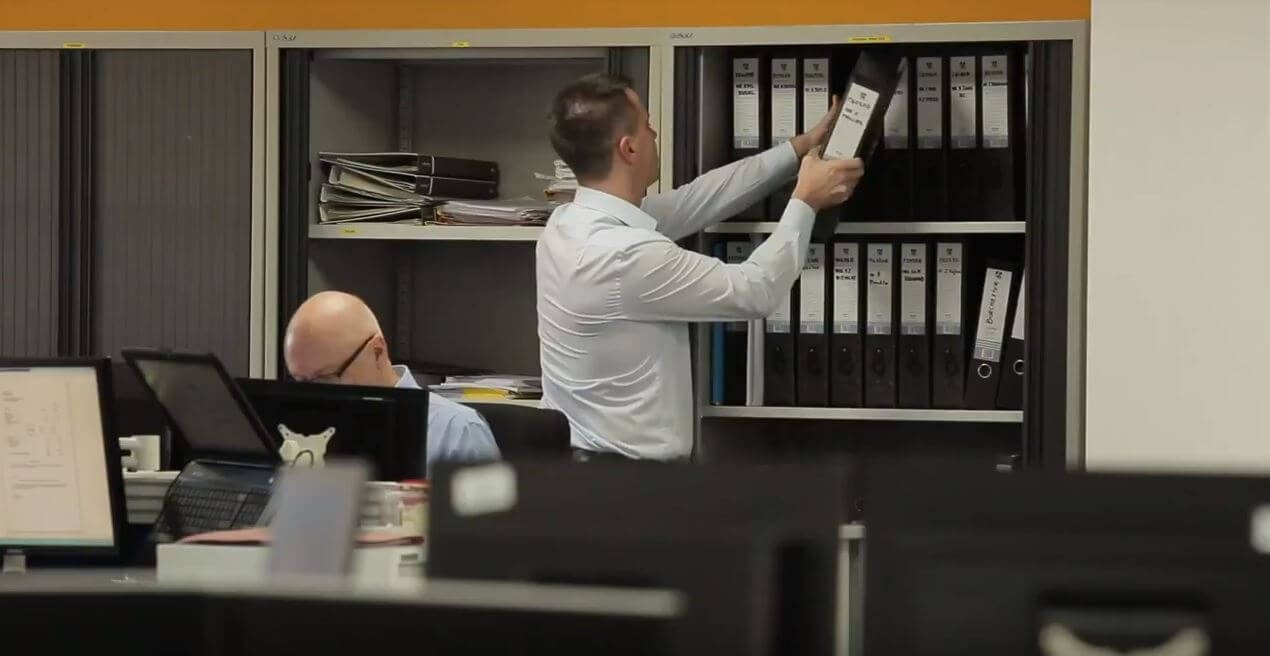 smartly-dressed man takes a file down from a shelf in a conventional looking office