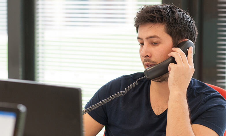 young man with short dark hair and stubble wearing a tshirt and speaking on the telephone