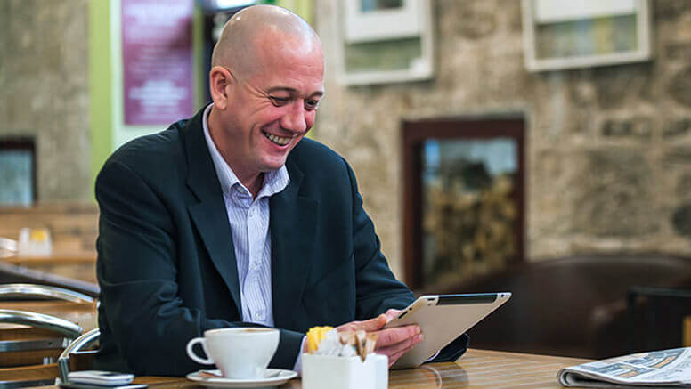 Smiling man wearing a suit and using a tablet at a café table