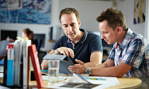 Two men in short-sleeved shirts looking at a tablet on a cluttered desk