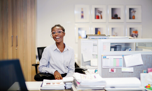 Smiling woman wearing pink glasses and a white shirt sitting in a bright office