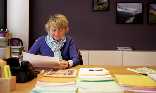 Older woman with blonde hair wearing a purple jersey and reading documents at a desk