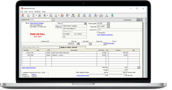 Laptop with sales invoice software on the screen