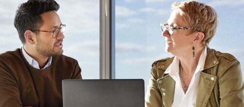 man and woman talking with a laptop between them