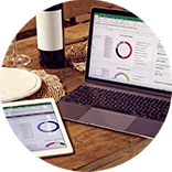 Roundel of a laptop and tablet displaying a budget planner on a wooden table set with plates, cutlery and a bottle of wine