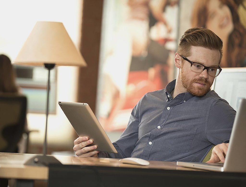 Un homme dans un bureau utilise un ERP paramétrable sur son ordinateur portable