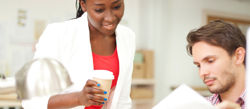 woman holding coffee looking at colleague's file