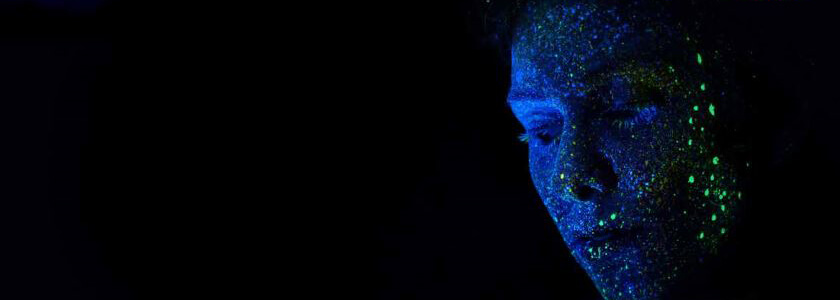 face flecked with luminous paint emerging from the dark