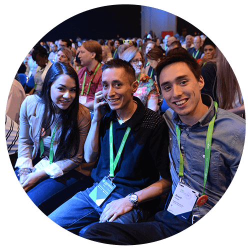 Three smiling young Sage delegates in the audience at an industry event