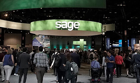 Crowd of business people walking towards a huge Sage stand at an industry event