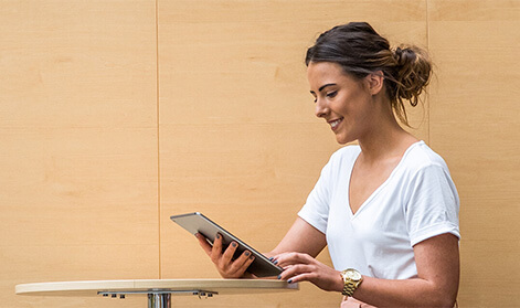 Young woman in a white t-shirt sitting at a table and looking at a tablet device