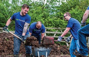 Group of men in Sage foundation t-shirts digging flowerbeds
