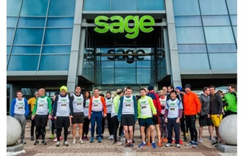 Group of runners in sports wear standing in front of the Sage headquarters