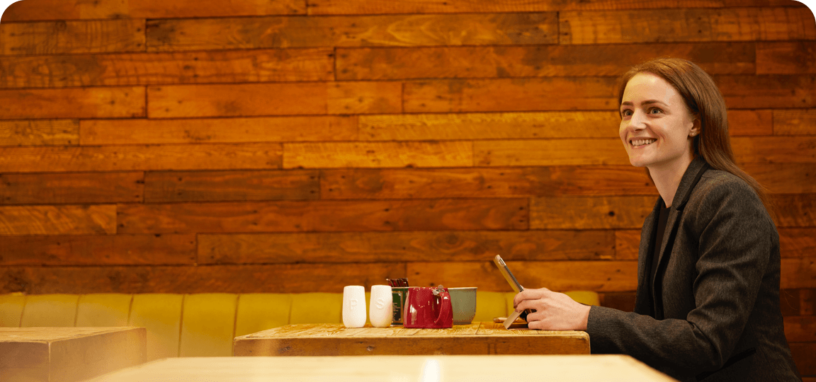 Smiling woman with red hair wearing a grey jacket sits at a café table