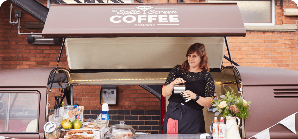 Woman in a black top and apron brews coffee in an independent coffee van