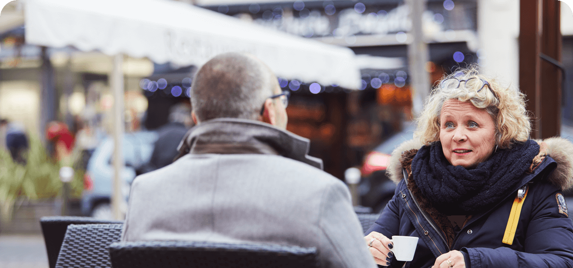 Woman in a thick winter coat sitting opposite a man and drinking coffee at a table outside a cafe