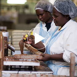 Screenshot from a video featuring two women working in a chocolate factory