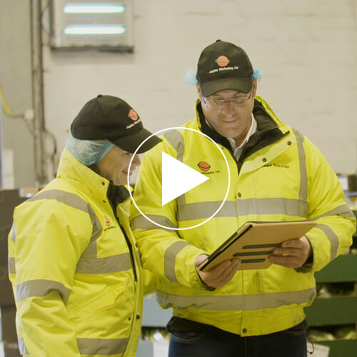 Screenshot from a video featuring a man and a woman in high-vis jackets looking at a clipboard