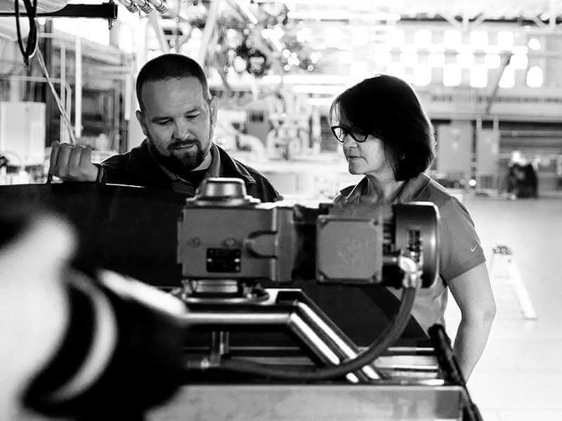 A man and a woman look at industrial machinery in a factory