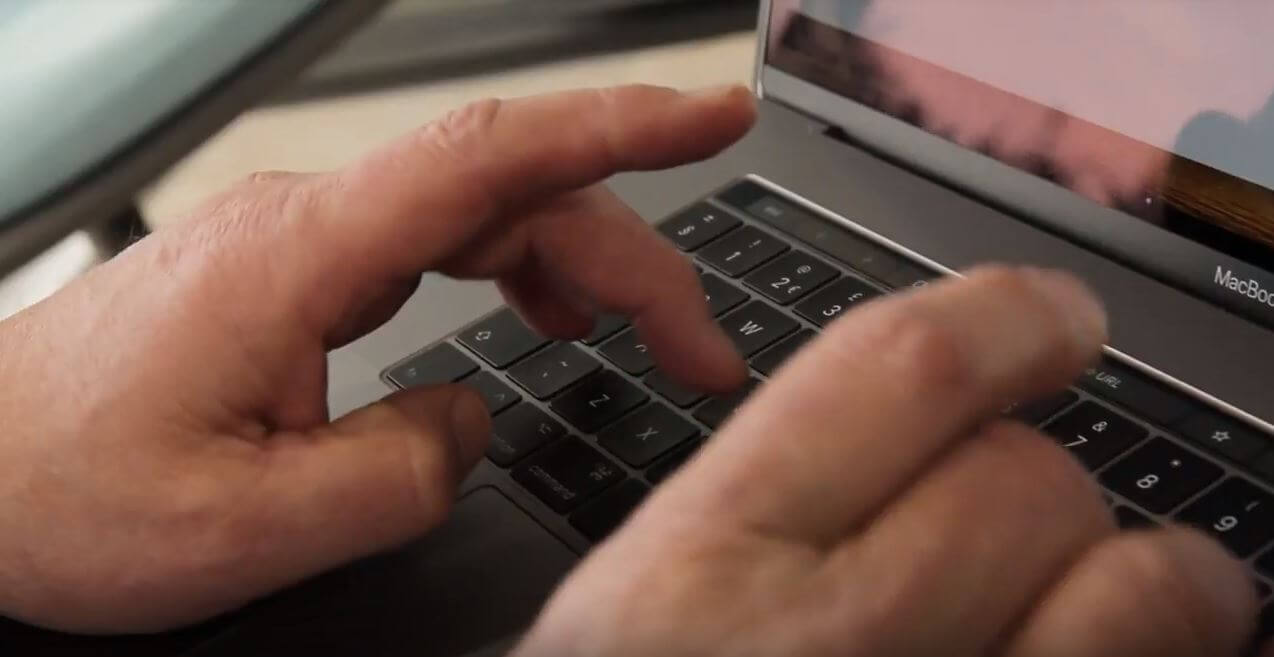 hands type on a laptop keyboard