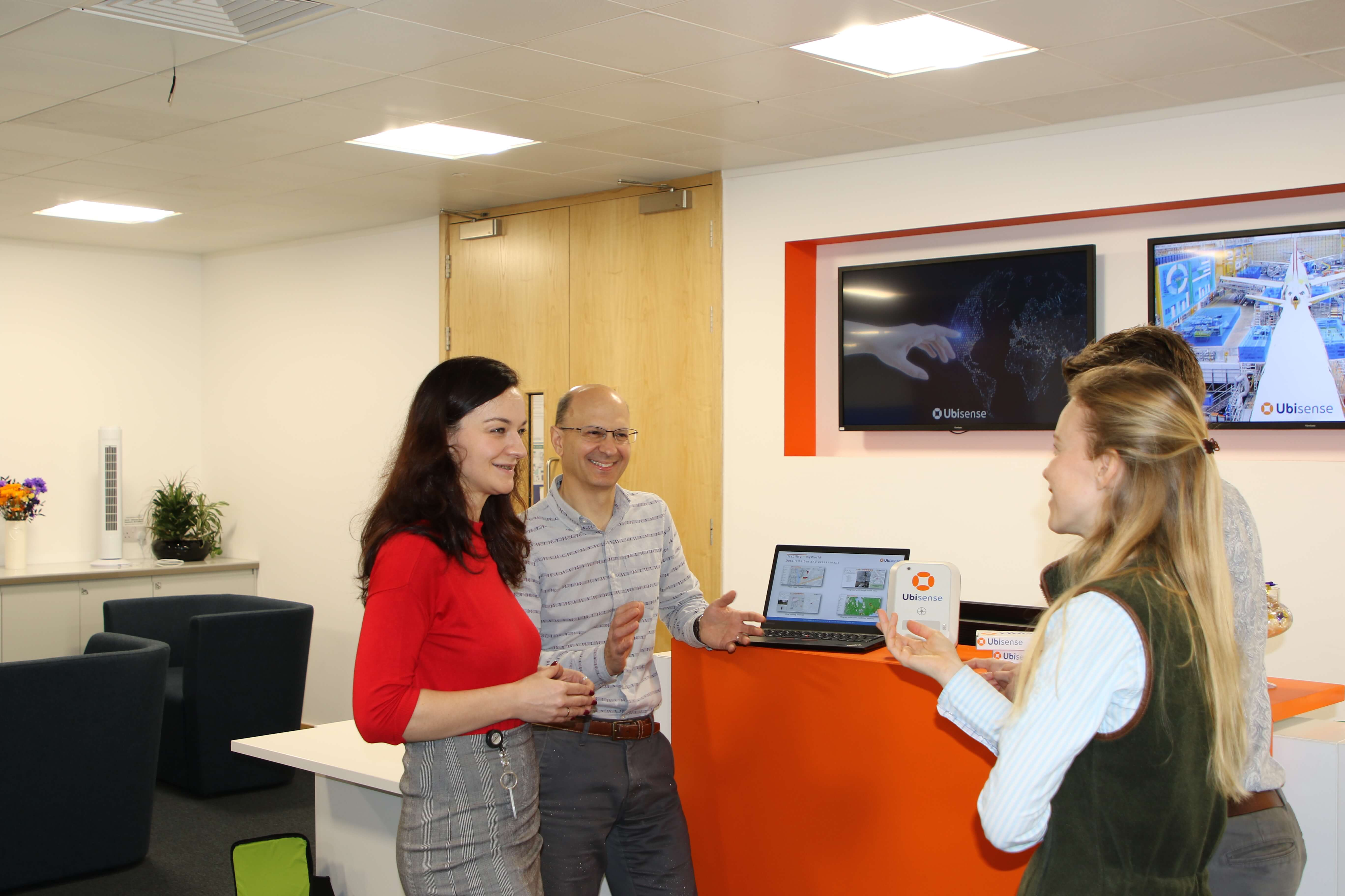 Four people standing and talking in the reception of a tech business
