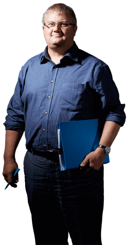 Man with neat grey hair, glasses and a blue shirt holding a blue ring-binder and a pen