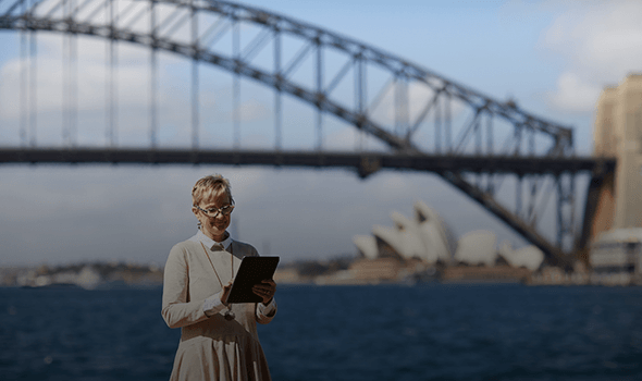 woman with short grey hair and glasses standing in front of Sydney Harbour Bridge and looking at a tablet