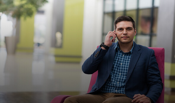 man with short dark hair and a blue blazer sitting in a modern lobby and speaking to Sage on his phone. OR    Sage customer sitting in a modern lobby and speaking on his phone