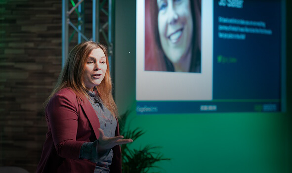 business expert standing on stage in front of a screen and addresing an audience at an event
