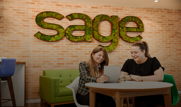 two young women sitting at a table and looking at a tablet with the Sage logo behind them on the wall