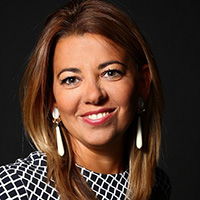Ingrid Cornaire, Sage Marketing Partner and Alliances Head, France. OR Woman with medium length, golden hair, wearing a black and white blouse and large earrings