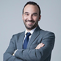 Juan Luis Ramos Casado, Sage Partner Marketing Manager, Spain. OR Man with short dark hair and beard, wearing a grey suit, white shirt and blue tie.