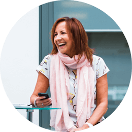 Roundel of an older woman with brown hair wearing a pink scarf laughing and holding a smartphone