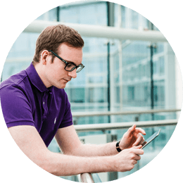 Roundel of a young man with brown hair wearing glasses and a purple polo shirt looking at his phone on an office balcony