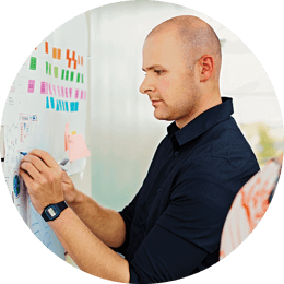 Roundel of a man with a shaved head sticking colored notes on a whiteboard